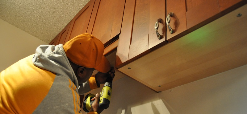 Handy man repairing cupboards